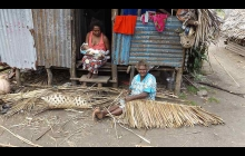 Villager weaving coconut roof cover